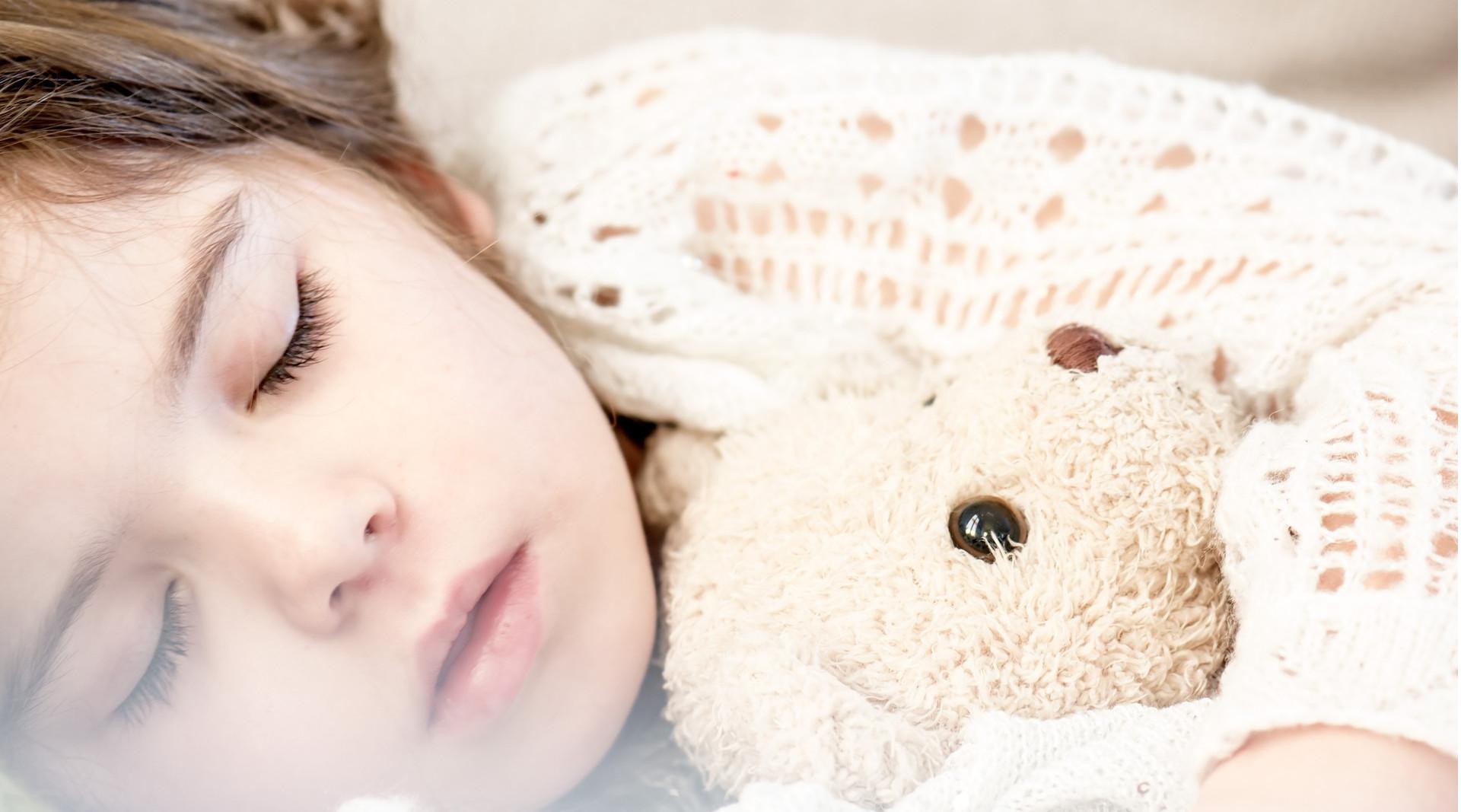 Mädchen schläft friedlich mit Teddy im Arm