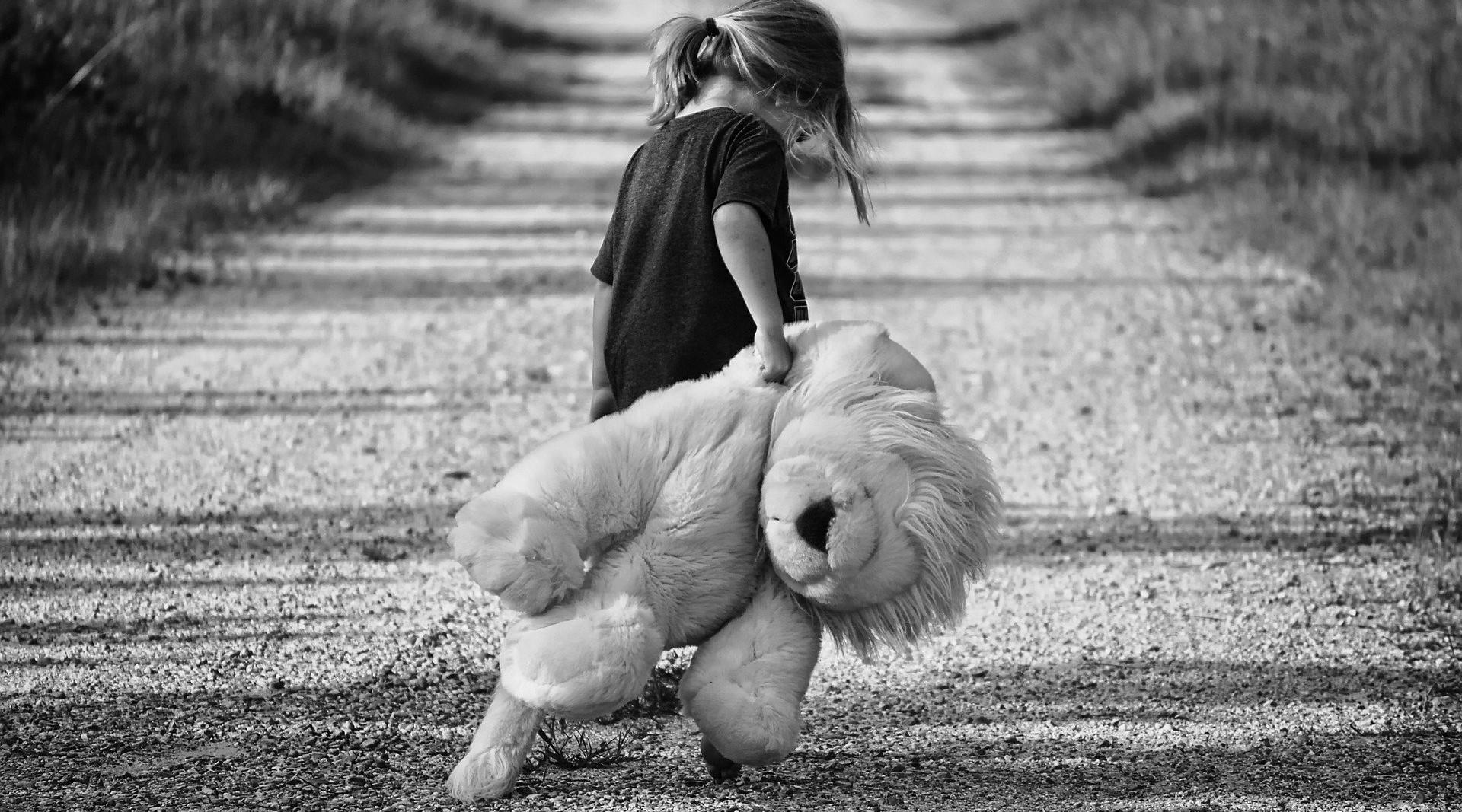 Mädchen zieht einen großen Stofflöwen hinter sich her